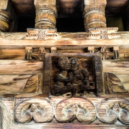 wooden carvings on the temple wall showing an amorous couple