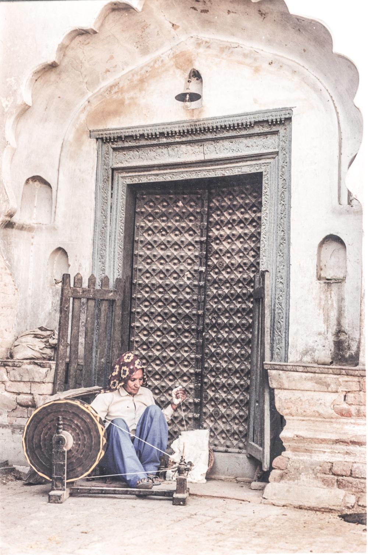 Old woman on Charkha (spinning wheel) preparing yarn